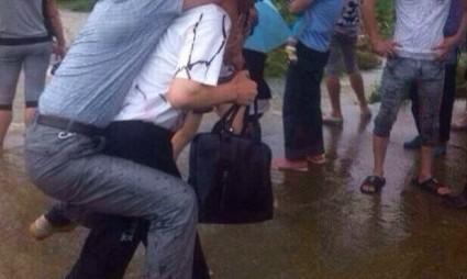 FOTO | Oficial chinez cărat în spate într-o zonă inundată, demis în urma unui scandal pe Internet