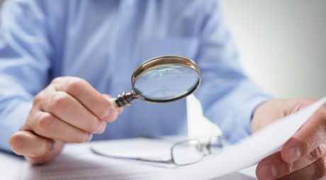 54428167 - businessman reading documents with magnifying glass concept for analyzing a finance agreement or legal contract