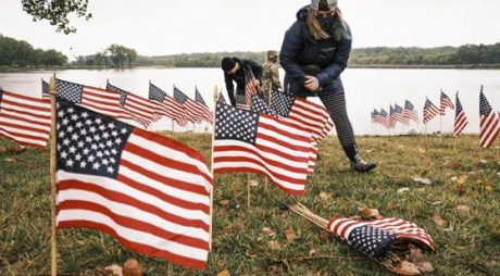Des Moines, IA  - A volunteer puts out American flags on the shore of Gray's Lake. About 25 volunteers braved cold and rainy weather Thursday to line the west end of Gray's Lake in Des Moines with American flags. The display of flags was a part of an annual event called the 9/11 Tribute Trail. About 3,000 flags were set out in memorial of the 3,000 people killed in the 9/11 terrorist attacks.  *UK Clients - Pictures Containing Children Please Pixelate Face Prior To Publication*,Image: 557321489, License: Rights-managed, Restrictions: RIGHTS: WORLDWIDE EXCEPT IN GERMANY, Model Release: no