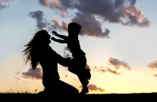 28077813 - a silhouette of a happy young boy child running into the arms of his loving mother for a hug, in front of the sunset in the sky.